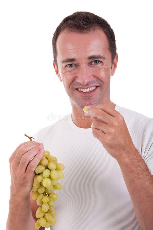 Het knappe mens eten groene druiven stock fotografie