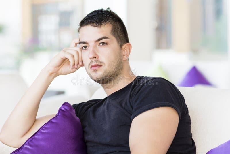 Het knappe mens ontspannen in een hotelhal op witte bank met purpere hoofdkussens stock fotografie