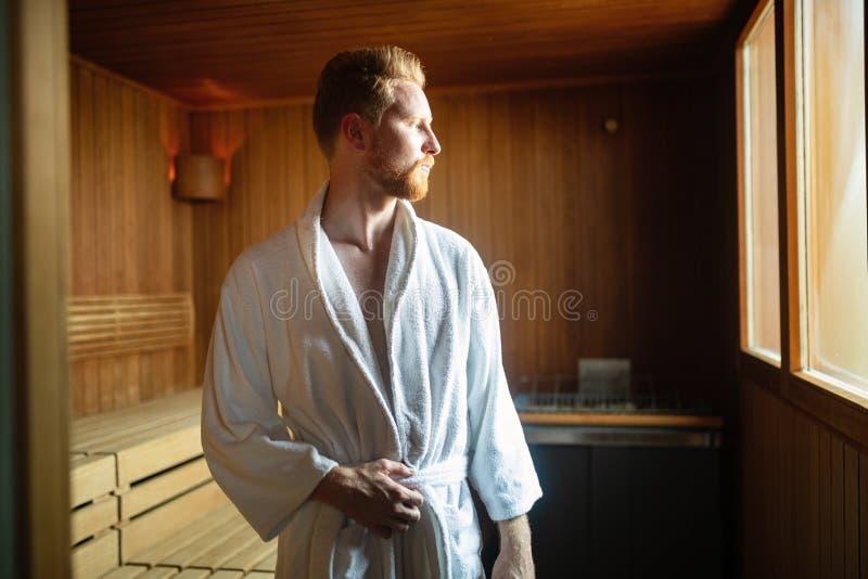 Het knappe mens ontspannen in sauna in kuuroordcentrum stock foto's