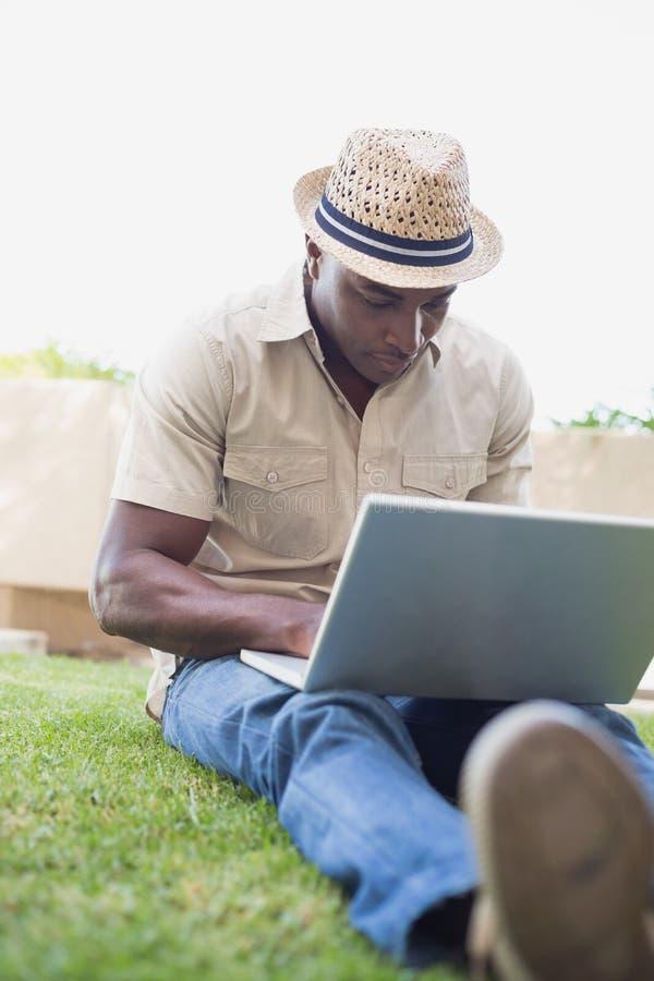 Het knappe mens ontspannen in zijn tuin die laptop met behulp van stock afbeeldingen