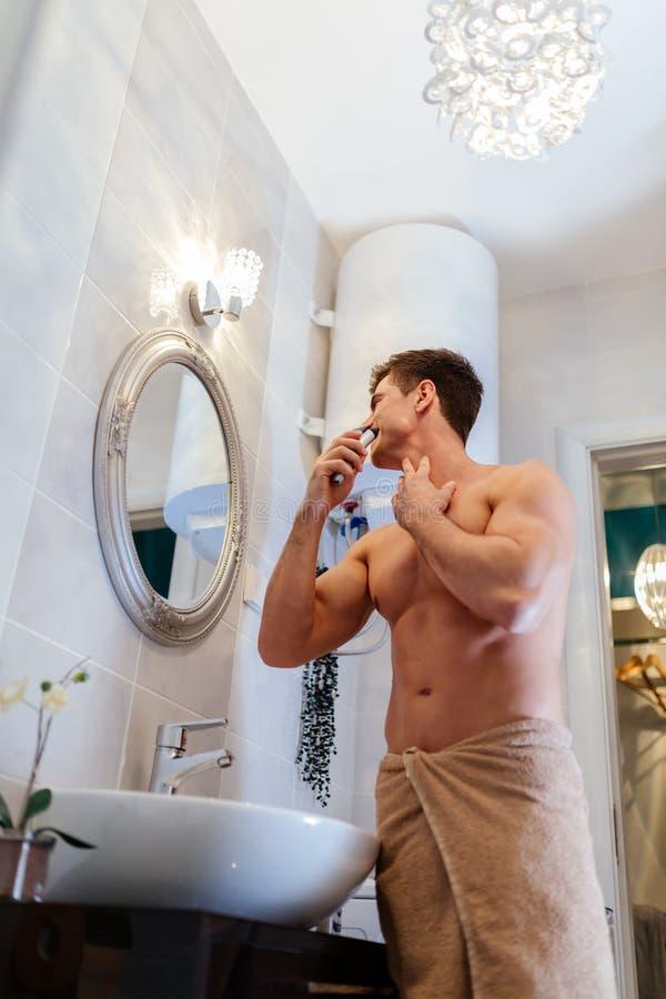 Het knappe mens scheren in badkamers royalty-vrije stock afbeelding