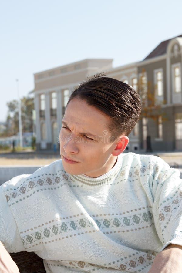 Het knappe mens stellen in witte sweater en het situeren op bank in stad stock foto's