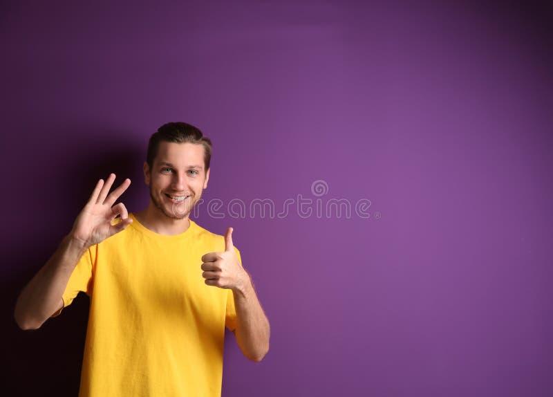 Het knappe mens tonen duim-omhoog en O.K. gebaar op kleurenachtergrond stock afbeeldingen