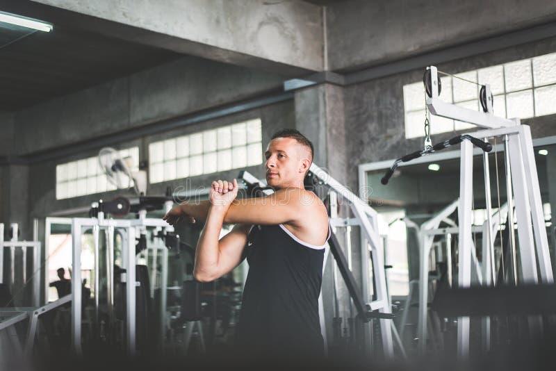 Het knappe mens uitrekken zich voor het opwarmen vóór training opleiding, Dwars geschikt lichaam spier in de gymnastiek stock foto
