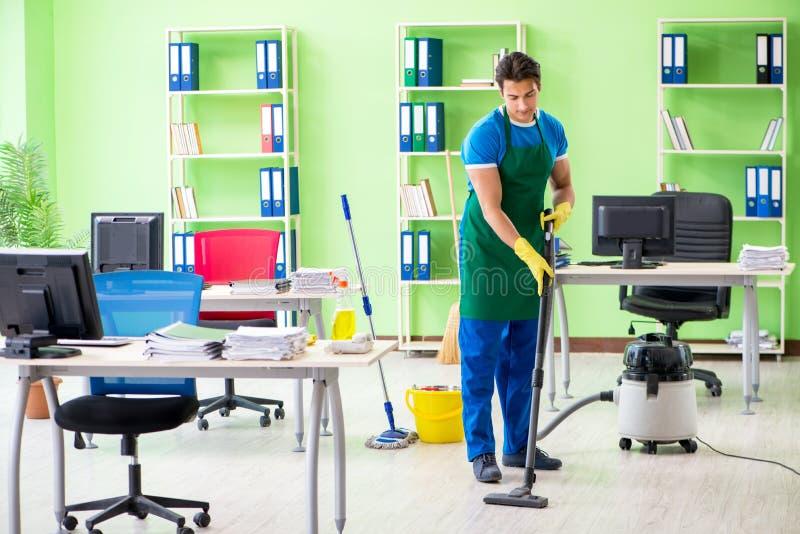 Het knappe mensen schoonmakende bureau met stofzuiger stock afbeelding