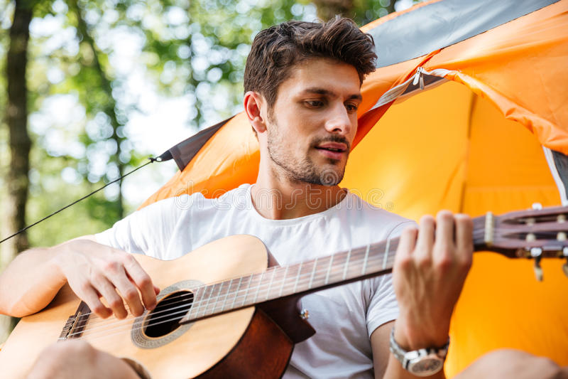 Het knappe mensentoerist zingen en het spelen gitaar bij toeristische tent royalty-vrije stock fotografie