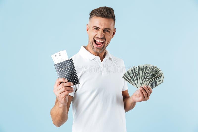 Het knappe opgewekte emotionele volwassen mens stellen geïsoleerd over blauw muur achtergrondholdingspaspoort met kaartjes en gel royalty-vrije stock afbeeldingen
