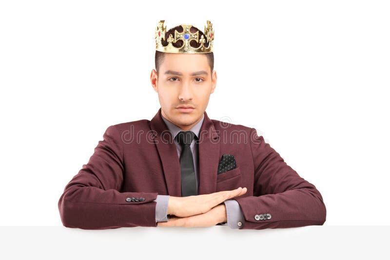 Het knappe prins stellen op een paneel met een diamantkroon stock afbeeldingen