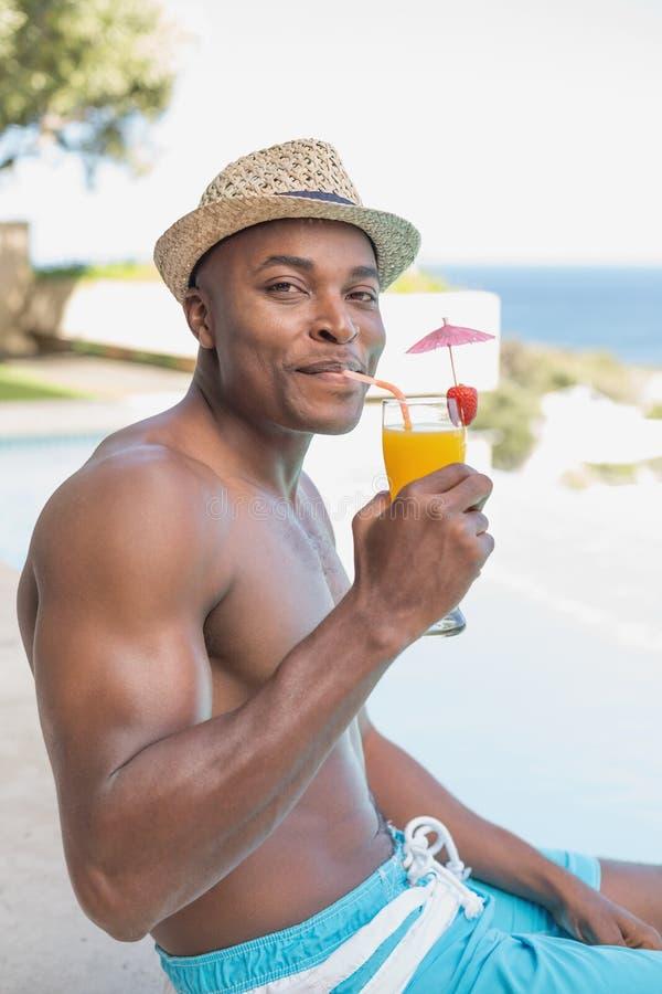 Het knappe shirtless mens ontspannen met cocktailpoolside stock fotografie