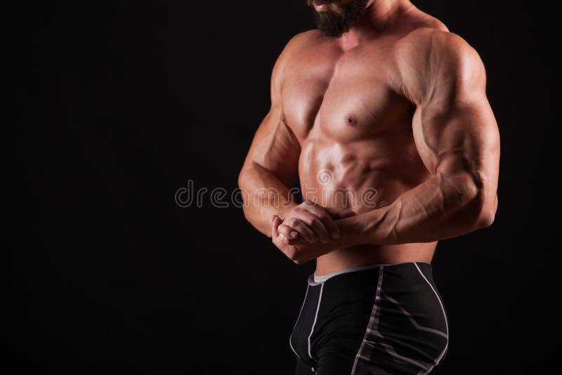 Het knappe spierbodybuilder stellen over zwarte achtergrond stock afbeeldingen