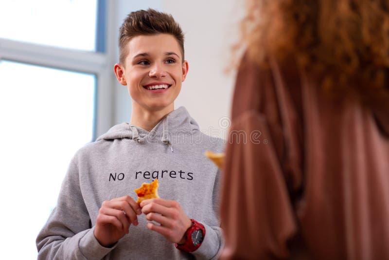 Het knappe stuk van de tienerholding van pizza terwijl het eten met krullend meisje stock foto's