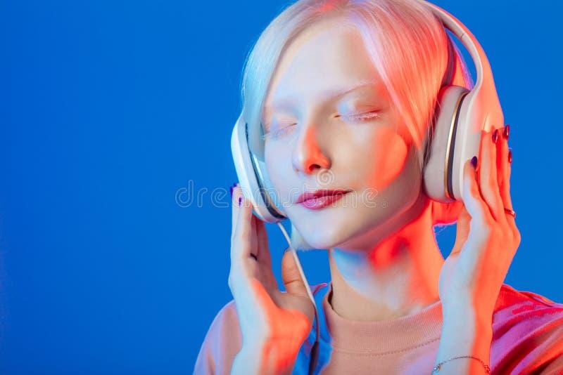 Het knappe vrouwelijke luisteren aan prettige muziek stock foto
