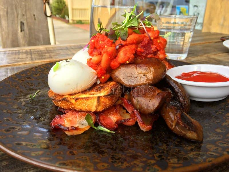Het knapperige bacon, stroopte eieren op toost met tomatensaus royalty-vrije stock foto