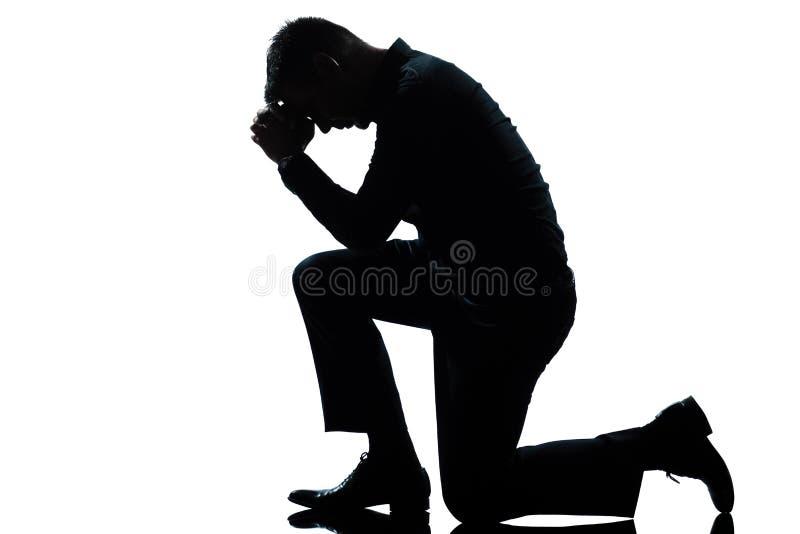Het knielen van de mens droefheid die volledige lengte bidt stock afbeelding