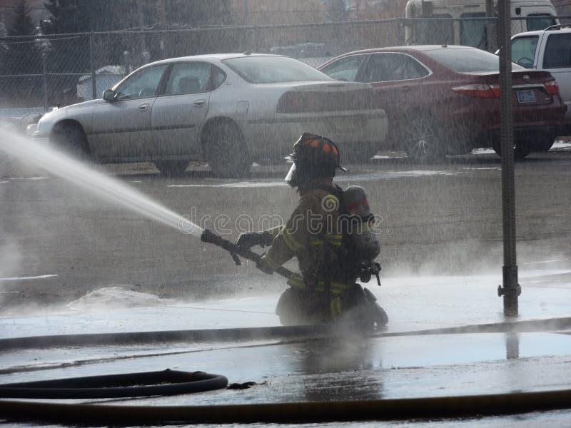 Het knielen in water het vechten brand stock fotografie