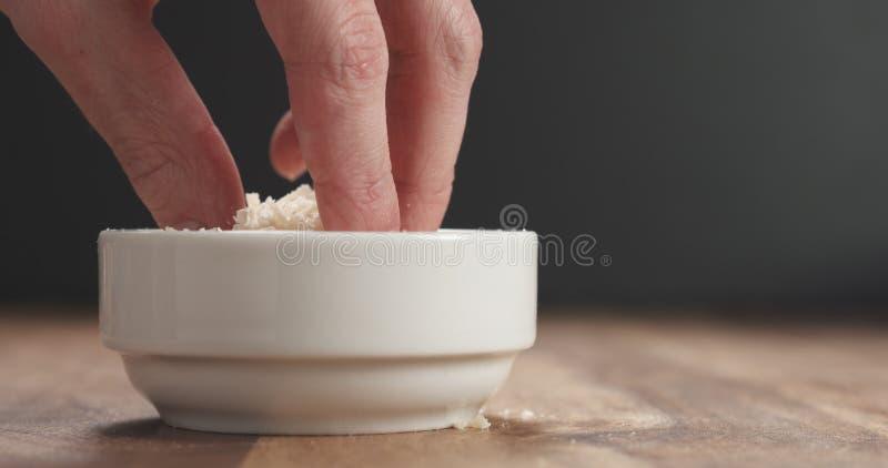 Het knijpen raspte oude parmezaanse kaas van witte kom op houten lijst stock afbeelding