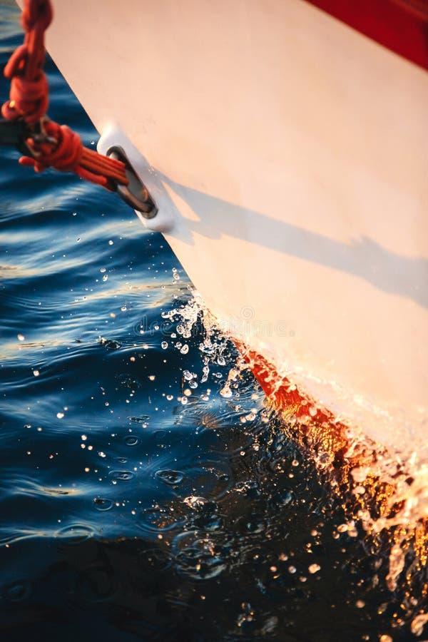 Het knipsel van de zeilbootboog door het water, voorwaarts, het zeil en het zeevaartdetail van het kabeljacht Zeilen, mariene ach stock foto