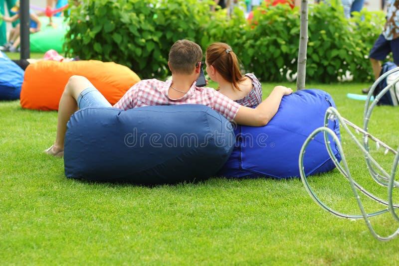 Het knuffelende paar op kinderspel geniet van picknick in het park stock afbeelding