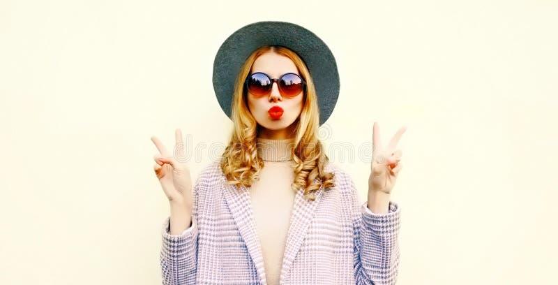 Het koele meisje die van het portretclose-up rode lippen blazen die luchtkus in ronde hoed verzenden stock afbeelding