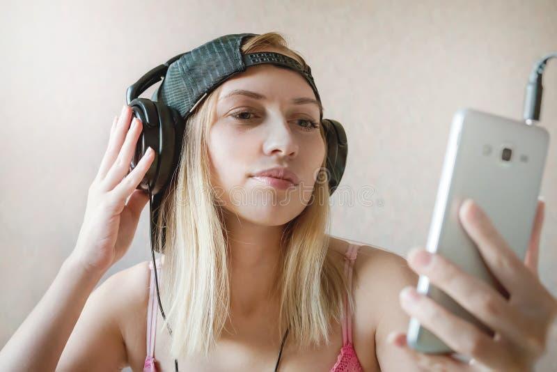 Het koele meisje luistert muziek in hoofdtelefoons over witte achtergrond Online Videopraatje Mededeling Het nemen van beelden va stock afbeelding