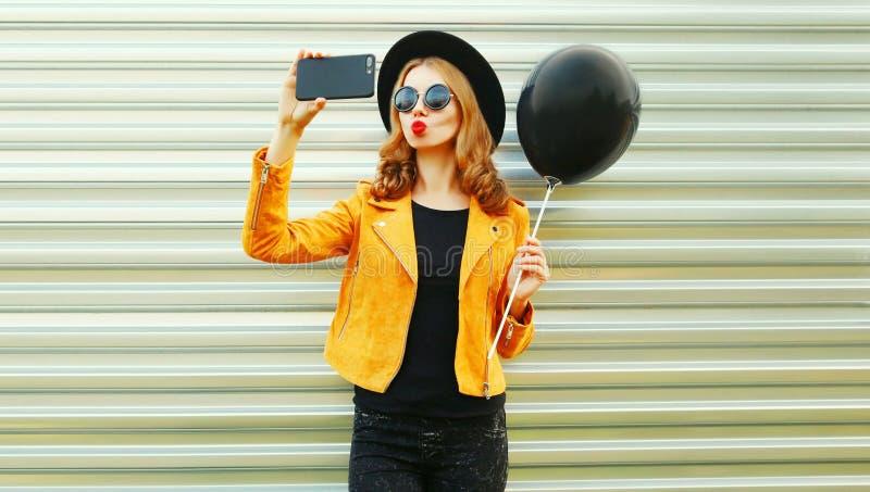 het koele meisje nemen selfie stelt door smartphone voor blazend rode lippen houdend de zwarte ballon van de heliumlucht royalty-vrije stock afbeelding
