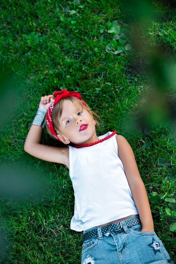 Het koele meisje openlucht liggen op het gras Kind in witte t-shirt, jeansborrels, rood halsband en verband op het hoofd De zomer stock fotografie