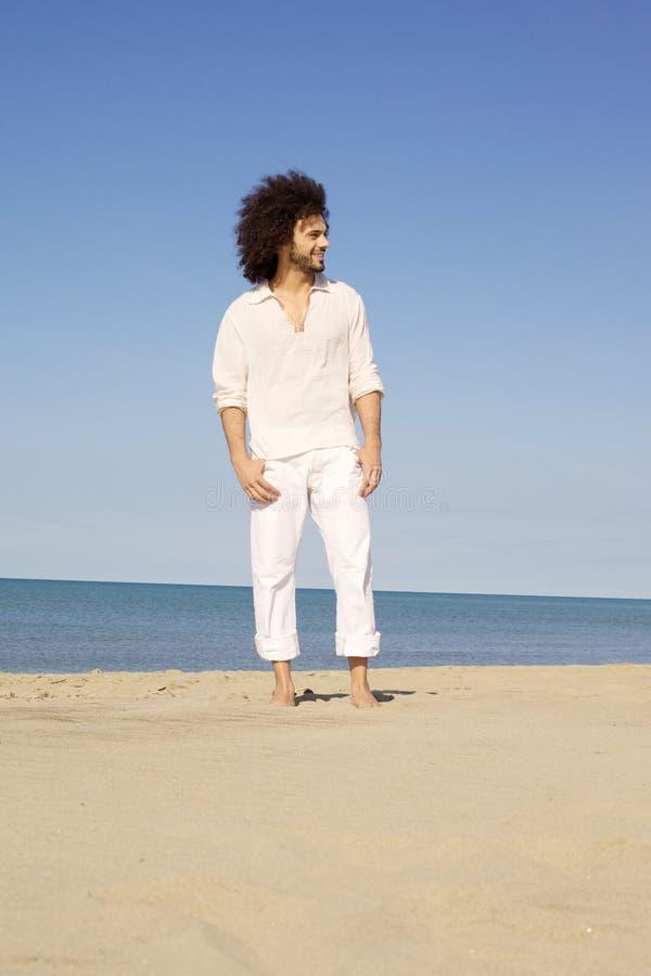 Het koele mens glimlachen die zich op zand voor de oceaan bevinden royalty-vrije stock foto