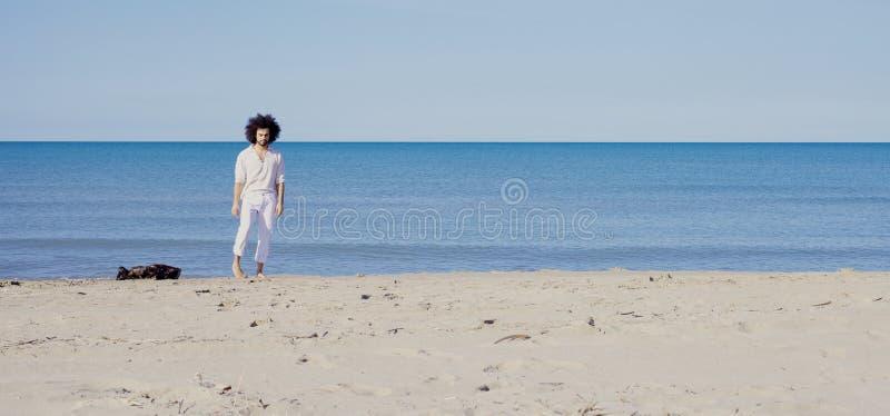 Het koele mens glimlachen die zich op zand voor wijd geschoten oceaan bevinden stock foto's