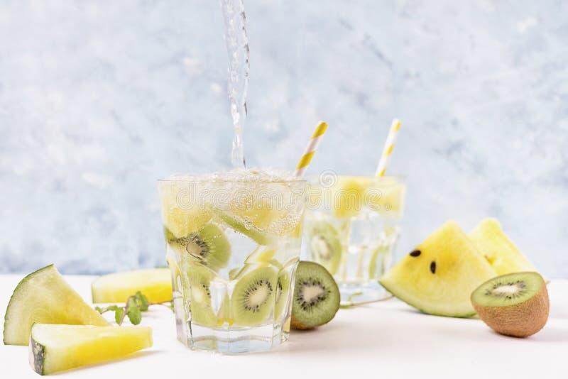 Het koele sodawater poring in gele watermeloen en kiwilimonade met ingredi?nten op heldere blauwe achtergrond motie Vegetarische  stock afbeeldingen