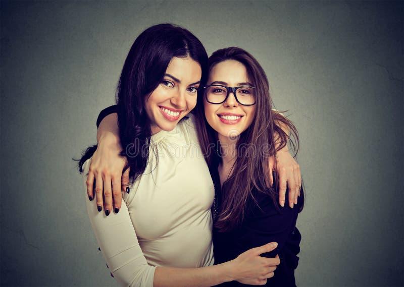 Het koesteren van gelukkige vrouwen die bij camera glimlachen stock afbeelding