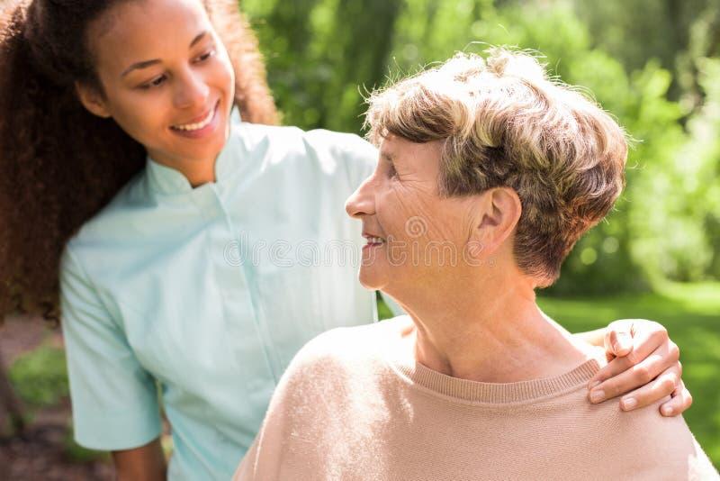 Het koesteren van oudere dame stock fotografie
