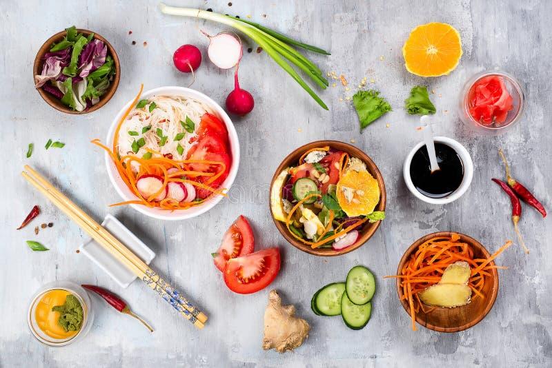 Het koken assorteerde plantaardige salades en Aziatische schotel op steenachtergrond, stock foto