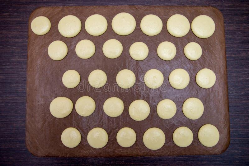 Het koken, het bakken, banketbakkerij en mensenconcept - chef-kok met macarons op ovendienblad bij bakkerijkeuken stock afbeelding