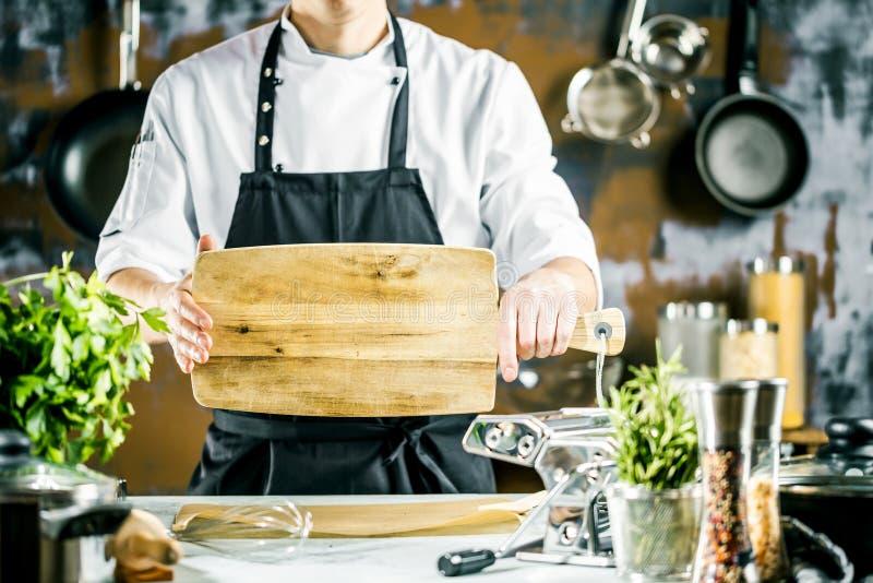 Het koken, beroep en mensenconcept - mannelijke chef-kokkok die voedsel maken bij restaurantkeuken stock afbeelding