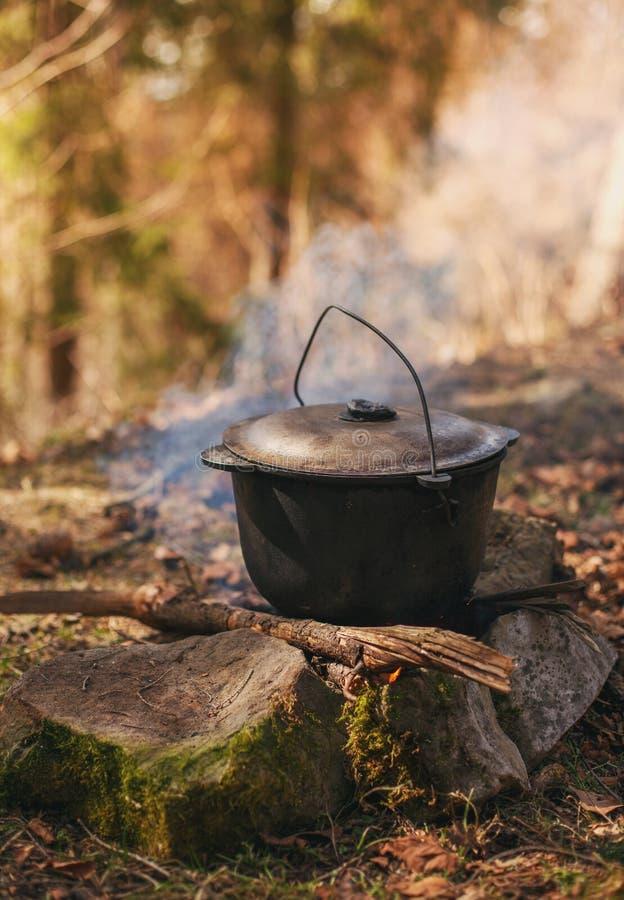 Het koken in de roetige ketel op de open brand in hout stock afbeeldingen