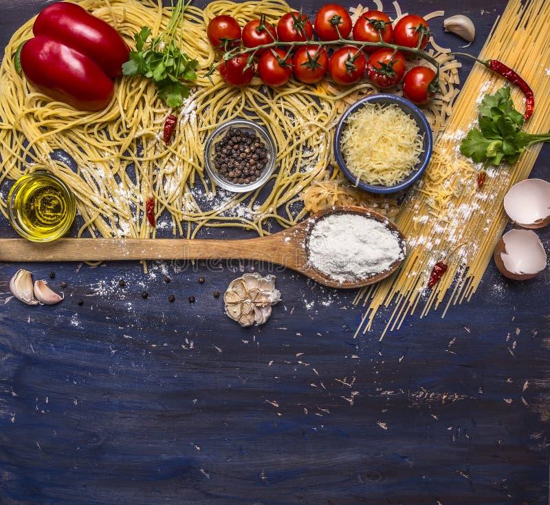 Het koken deegwarenconcept met tomaten, parmezaanse kaaskaas, peper, kruiden, bloem, knoflook, houten lepel, grens, met tekstgebi royalty-vrije stock foto's
