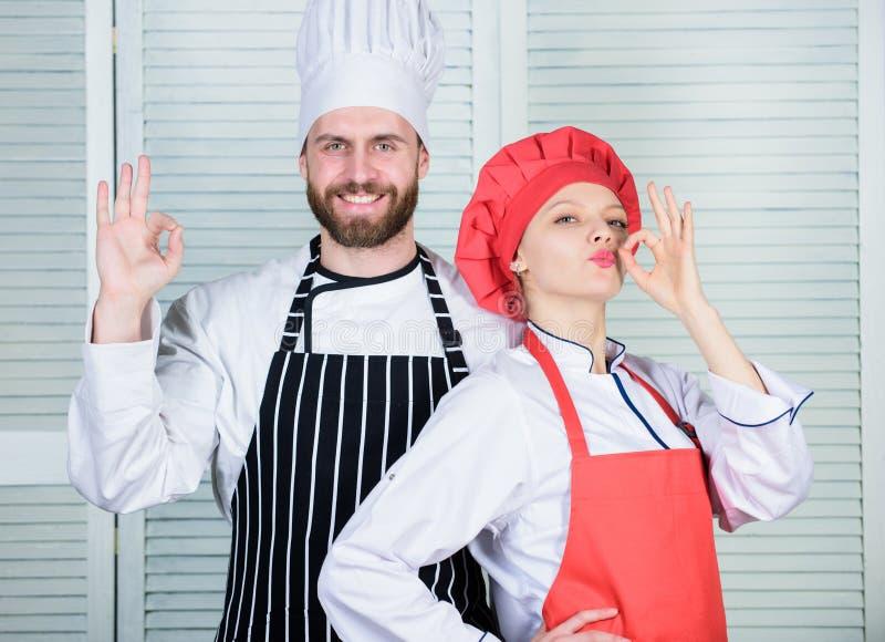 Het koken met uw echtgenoot kan verhoudingen versterken Groepswerk in keuken Het kokende diner van het paar vrouw en gebaarde man stock afbeeldingen