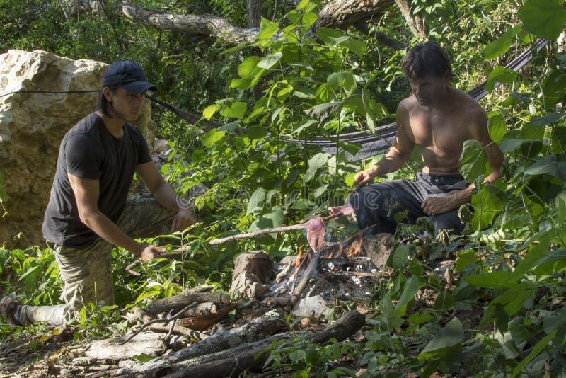 Het koken over primitief kampvuur in de wildernis royalty-vrije stock afbeeldingen