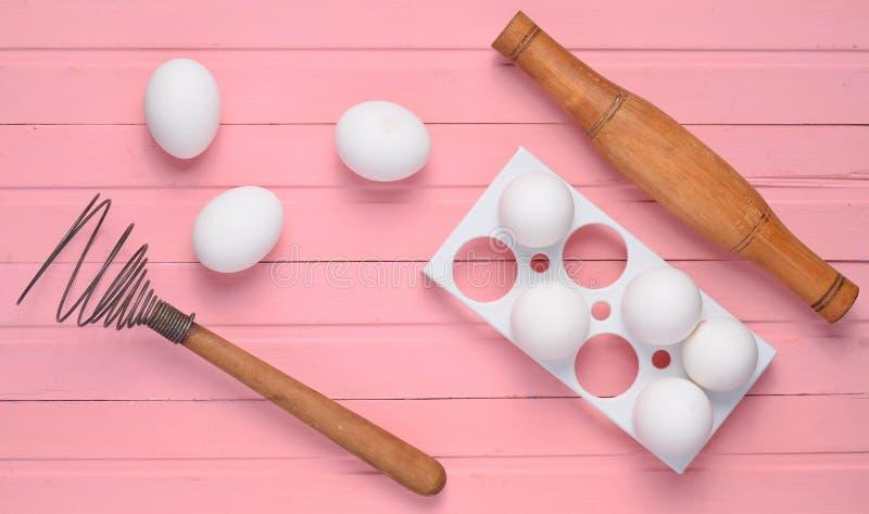 Het het koken procédé Het plastic dienblad met witte eieren, deegrol, zwaait op een roze houten lijst Hoogste mening stock foto