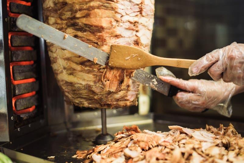 Het koken shawarma en ciabatta in een koffie Een mens in beschikbare handschoenen snijdt vlees op een vleespen stock afbeeldingen