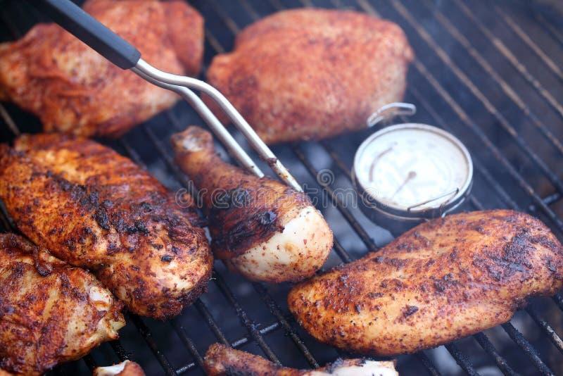 Het koken stukken van kip bij de barbecuegrill stock afbeelding