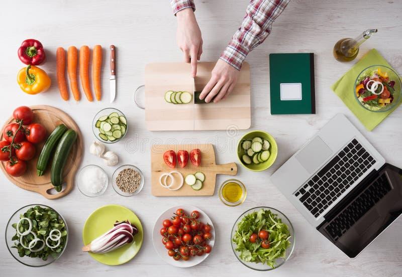 Het koken thuis met online recepten stock foto's