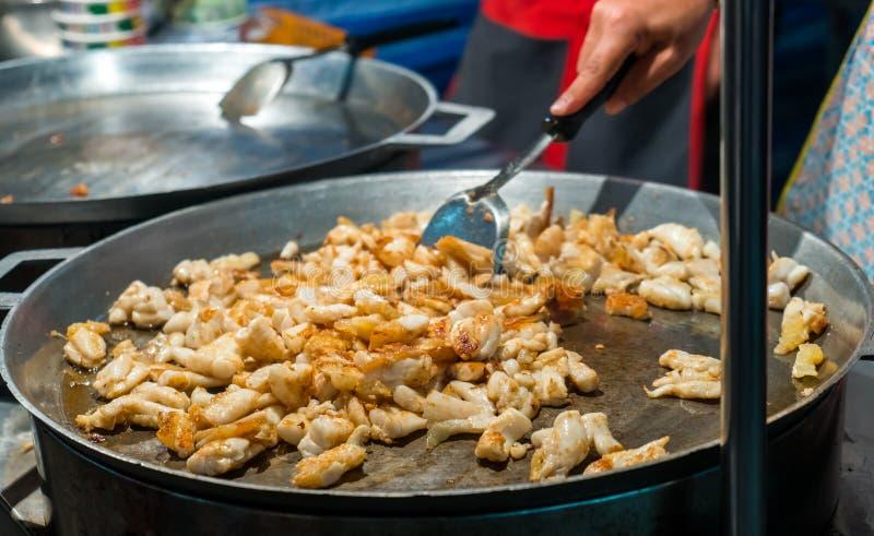 Het koken van het braden pijlinktvis met ei in een grote pan bij marktkraam royalty-vrije stock afbeelding