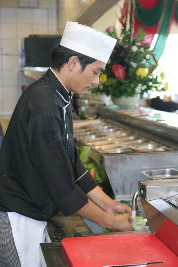 Het koken van de chef-kok bij restaurantkeuken stock fotografie