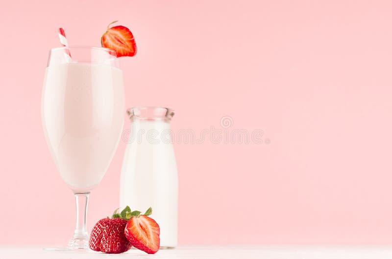 Het koken van de lente verse roze milkshake met aardbei, bootle van melk op zachte roze achtergrond, exemplaarruimte stock afbeeldingen