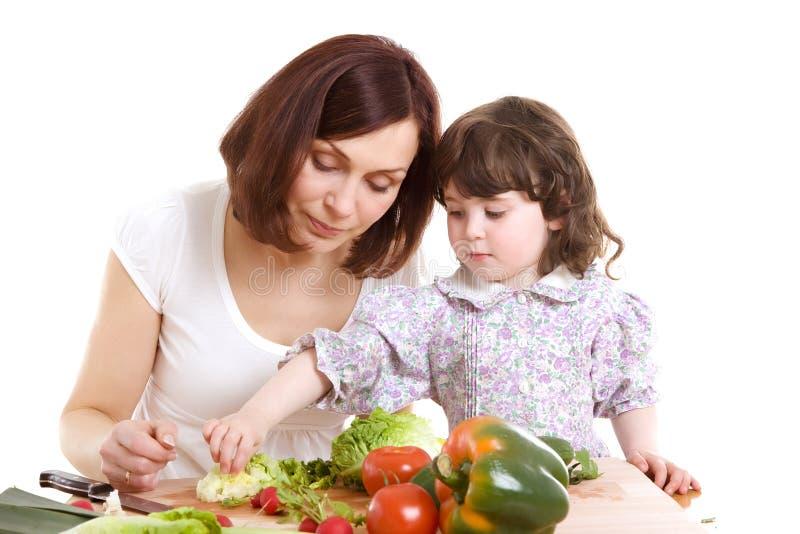 Het koken van de moeder en van de dochter bij de keuken stock foto