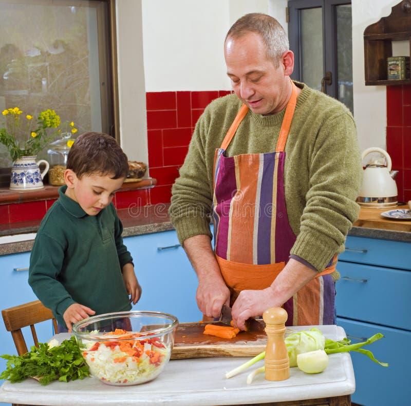 Het koken van de vader en van het kind stock afbeeldingen