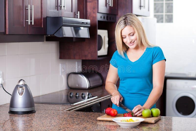 Het koken van de vrouw in keuken stock foto's