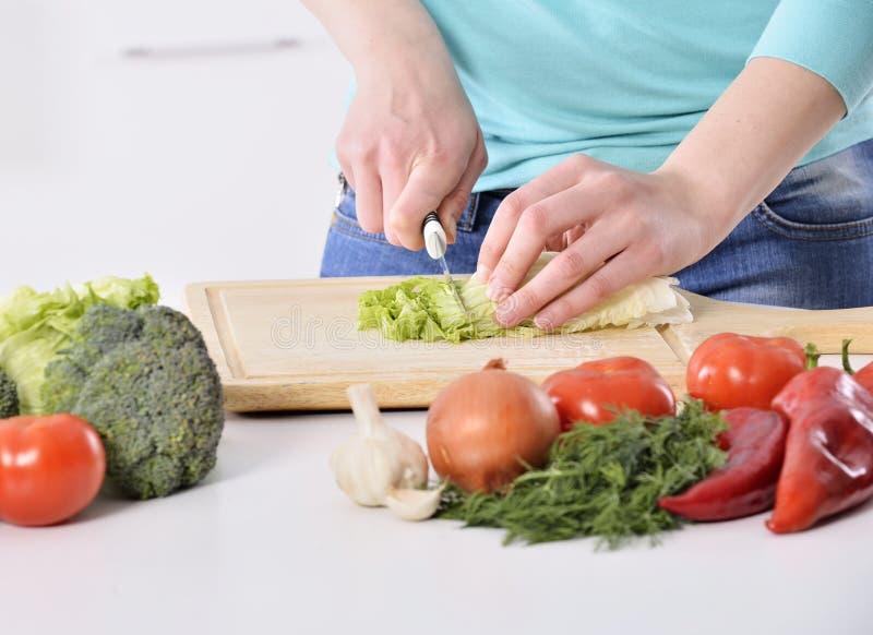 Het koken van de vrouw in nieuwe keuken die gezond voedsel met groenten maakt stock foto