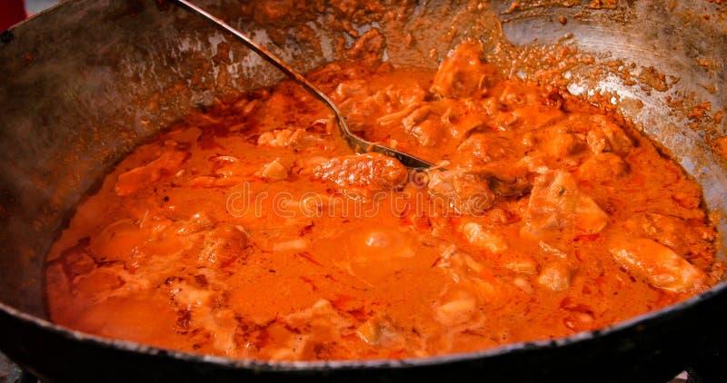 Het koken van een vleeshutspot met tomatensaus in een grote wok royalty-vrije stock afbeeldingen